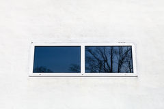Glass window in white painted wall. Of country house Royalty Free Stock Photos