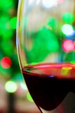 Glass of wine 003. Glass of red wine on the background of colored lights Stock Images