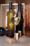 Glass of wine. A glass of sparkling wine with three bottles right behing it and some corks Stock Images