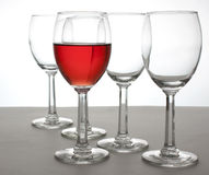 Glass of Wine. A glass of White Zinfandel and four empty wine glasses Royalty Free Stock Photos