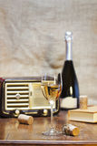 Glass of wine. A glass of white wine with a bottle on the background and a vintage radio,a book on an old table Royalty Free Stock Photography