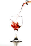 Glass of wine. Pouring rose wine in glass isolated on white background Royalty Free Stock Images
