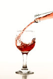 Glass of wine. Pouring rose wine in glass isolated on white background Stock Photo