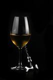 Glass of wine. Close up of a glass of wine and a corkscrew over black background Stock Photo