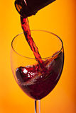 Glass of wine. Pours wine on a bright background Royalty Free Stock Image