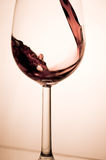 Glass of wine. Wine pouring into a glass, studio shot Royalty Free Stock Images