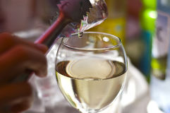 Glass of wine. Ice tong holding an ice cube over a glass of wine Stock Images