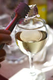 Glass of wine. Ice tong holding an ice cube over a glass of wine royalty free stock images