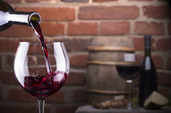 Glass of wine against a brick wall. Glass of wine and some fruits, bottle of wine, cheese against a brick wall Royalty Free Stock Photography