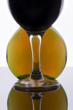 Glass with wine against a round bottle Royalty Free Stock Photo