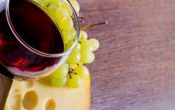 Glass of wine amid grapes and piece of cheese Copy-space. Food closeup background. Glass of wine amid grapes and piece of cheese. Glass of wine in focus. Copy stock image