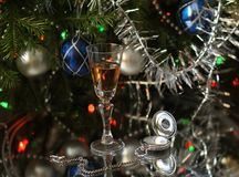 A glass of wine and an antique silver clock next to fir branches decorated with tinsel and glass balls. Close-up. A glass of wine and antique silver clocks next stock images