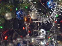 A glass of wine and an antique silver clock next to fir branches decorated with tinsel and glass balls. Close-up. A glass of wine and antique silver clocks next royalty free stock image