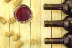 Glass of wine on background of bottles and corks Stock Images