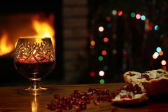 A glass of wine on the background of the fireplace and Christmas tree Stock Photography