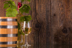 Glass of wine with barrel white bottle behind grapeleaves. And dark wooden background Royalty Free Stock Image