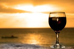 Glass of wine on the beach. Glass of wine on the see shore in a lovely evening stock image