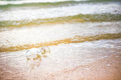 Glass wine on the beach and sea water flow in golden hour royalty free stock photo