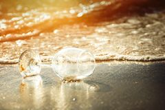 Glass wine on the beach and sea water flow in golden hour stock photos