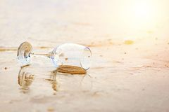 Glass wine on the beach and sea water flow in golden hour royalty free stock photography