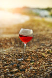 Glass of wine on the beach at sunset. Glass with red wine on the beach at sunset. Beach covered with small pebbles. Beautiful light of the setting sun in the Royalty Free Stock Photo