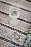 Glass of wine on the beach. Glass of white wine stands on the wooden boards of the coast from a pebble royalty free stock photo