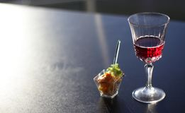 Glass with wine on the black top in office royalty free stock photography