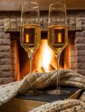 Cozy scene before fireplace with glass of wine, book and wool warm scarf. Glass of wine, book and warm wool scarf near cozy fireplace in country house, winter royalty free stock image