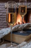 Cozy scene before fireplace with glass of wine, book and wool warm scarf. Glass of wine, book and warm wool scarf near cozy fireplace in country house, winter stock photography