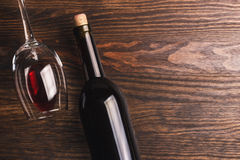 Glass with wine and bottle with cork, wooden background. Glass with red wine and bottle with cork, wooden background royalty free stock images