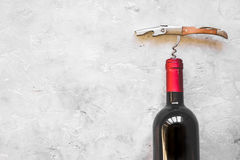 Glass wine bottle and corkscrew on concrete background top view Stock Photography