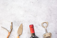Glass wine bottle and corkscrew on concrete background top view Royalty Free Stock Photography