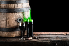 Glass of wine with bottle and old oak barrel Royalty Free Stock Images