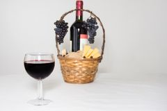A glass of wine. A bottle of red wine, grapes and picnic basket with cheese slices on white background. stock photography