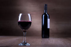 Glass of wine with a bottle on a wooden backgound Royalty Free Stock Photography