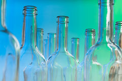 Glass wine bottlenecks on blue background Royalty Free Stock Photography