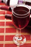 Glass of wine with bottles Stock Photography