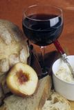 Glass of wine with bread, peach and cheese royalty free stock image
