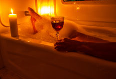 A glass of wine and bubble bath. A glass of red wine by candle light and a bubble bath Royalty Free Stock Image