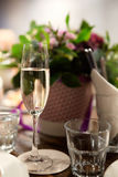 A glass of wine with bubbles on the background of flowers. At the banquet table in a restaurant Stock Image