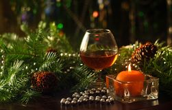 A glass of wine, a burning candle and decor of fir branches and cones. stock images