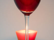 Glass of wine and a candle. Fire candle through the leg with a glass of red wine stock image