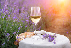 Glass of wine on the canvas cloth. Glass of wine in front of lavender field on the background. Sunset light over glass of wine on the canvas cloth. Alcohol and stock image