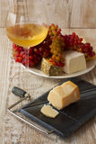 Glass of wine, cheese and fresh grapes on a wooden backgro Stock Photography