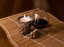 A glass of wine, cinnamon, pine cone. And a burning candle Royalty Free Stock Image