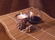 A glass of wine, cinnamon, pine cone. And a burning candle Royalty Free Stock Photos