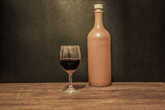 Glass of wine with clay bottle Stock Photos