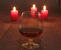 Glass of wine or cognac and red candle on a wooden background. Royalty Free Stock Images