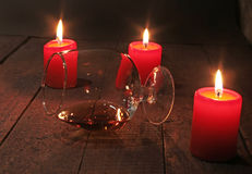 Glass of wine or cognac and red candle on a wooden background. Royalty Free Stock Photography