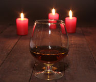Glass of wine or cognac and red candle on a wooden background. Stock Photos